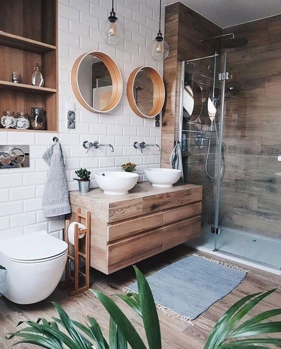 a lovely contemporary bathroom with a wood clad shower space, a wooden vanity, mirrors in wooden frames, laminate floor, a niche clad with wood