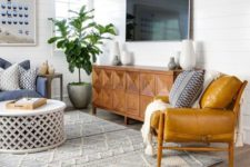 a mid-century modern living room with mustard and blue furniture, an inlay sideboard and a rug with boho embroidery