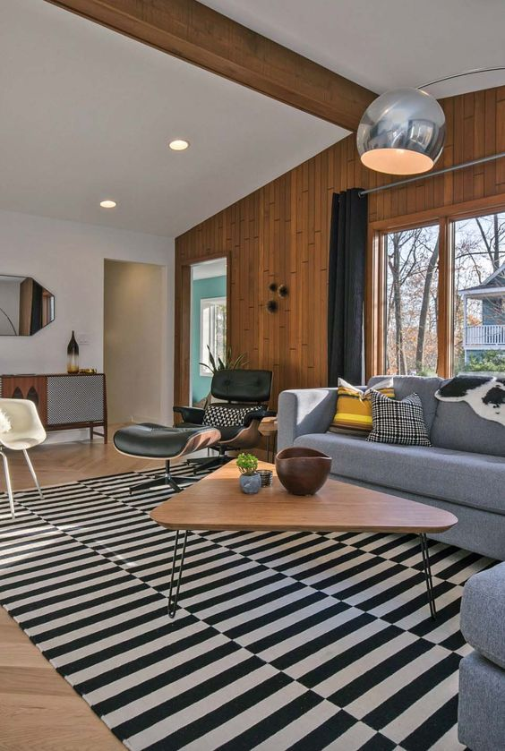 a mid-century modern living space with a striped rug takign over it, black, white and grey furniture, lamps and a hairpin leg table