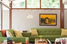 a mid-century modern room with green furniture, neon green and rust textiles, light-colroed wood and skylights