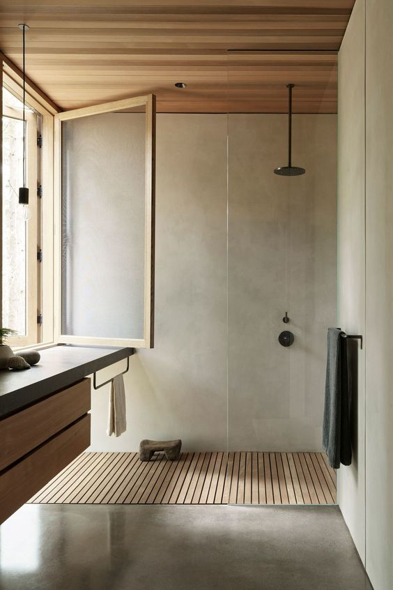 a minimalist bathroom clad with light stained wood and with concrete, with black fixtures and a vanitu with a concrete countertop