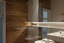 a minimalist bathroom clad with light stained wood, with a mirror wall and white appliances is pure luxury and invites in
