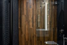 a minimalist bathroom clad with small black tiles and with wood-like tiles for a super elegant and contrasting look