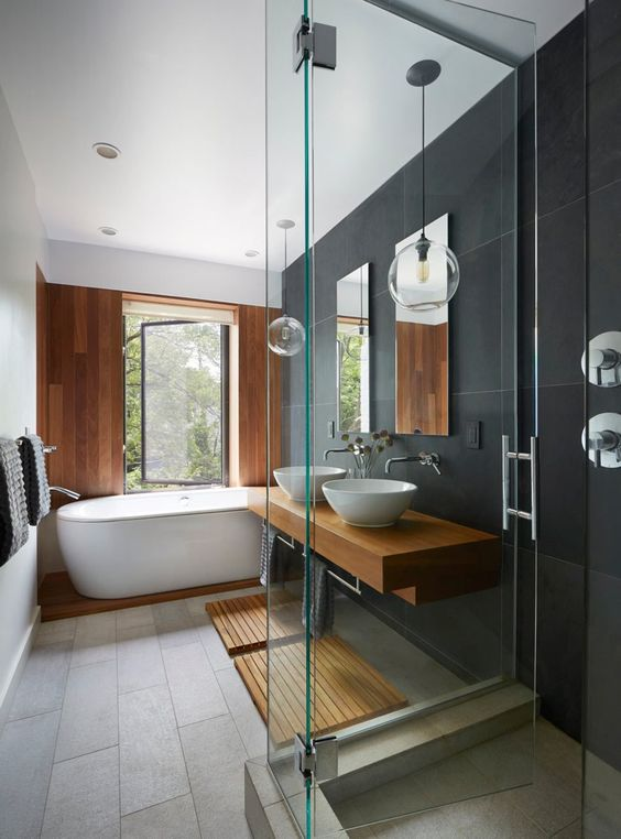 a minimalist bathroom done with grey and black tiles, with a wooden accent wlal and platform, a wooden vanity and mats plus pendant lamps