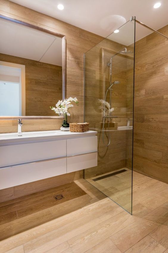 a minimalist bathroom fully clad with wood, with a glass-enclosed shower space, a floating white vanity and a mirror