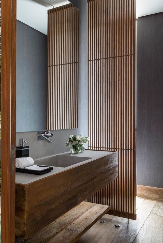 a minimalist bathroom with a planked screen, a wooden vanity with a built-in sink, a shelf and a wooden floor is a chic space
