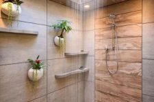 a minimalist bathroom with neutral tiles and wood, with a skylight over the shower space and potted plants on the wall