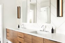 a modern bathroom done with black and white tiles, with a stained wooden vanity and a trio of mirrors, with built-in lights