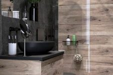 a moody bathroom clad with light stained wood and with black tiles, a chic vanity with a black sink and black fixtures is a lovely space