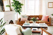 a neutral living room with a brown leather sofa, creamy furniture, potted greenery, mirror and a firewood storage space