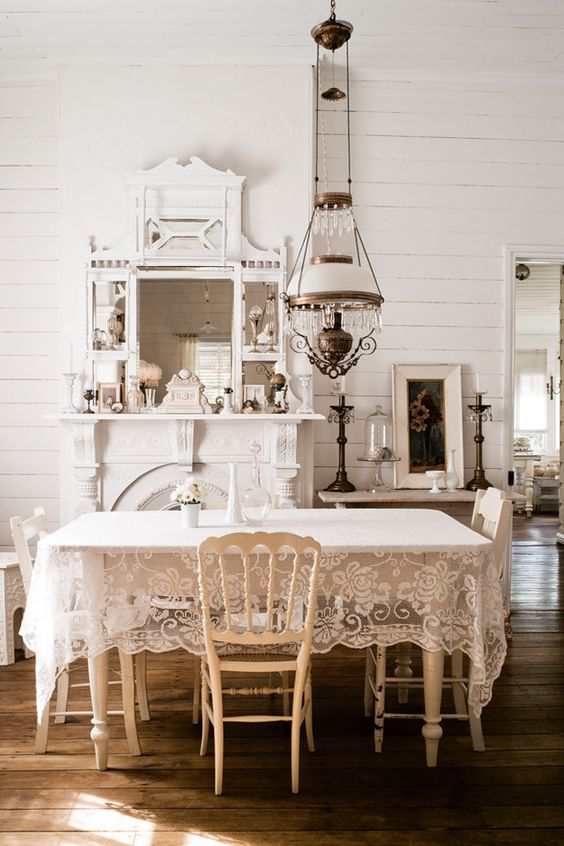 a neutral shabby chic dining room with white furniture, a vintage lamp, a large mirror and a faux fireplace and a lace tablecloth