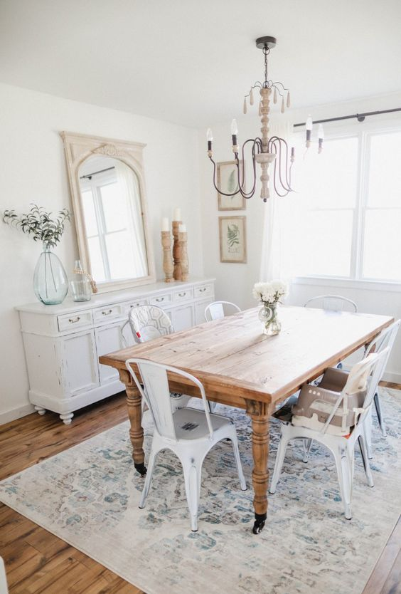 a neutral shabby chic meets rustic dining room with a wooden table, white metal chairs, a shabby chic sideboard and a vintage chandelier
