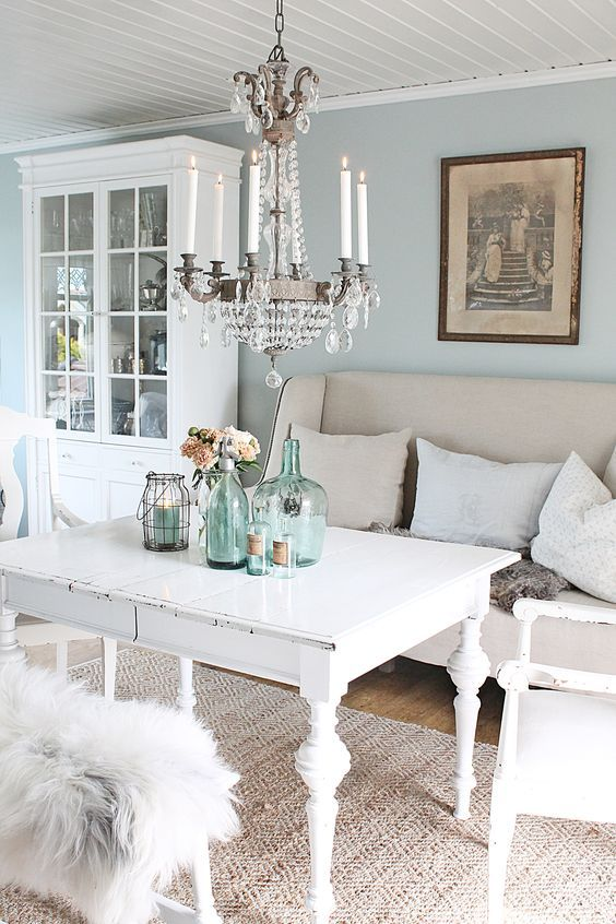 a pastel shabby chic dining room with blue walls, white shabby chic furniture,a  crystal chandelier, blue bottles and jars