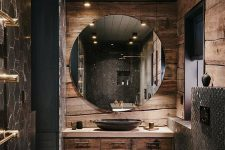 a refined moody bathroom clad with rough wood, with a black planked wooden ceiling, a round mirror, a tiled floor and matching walls