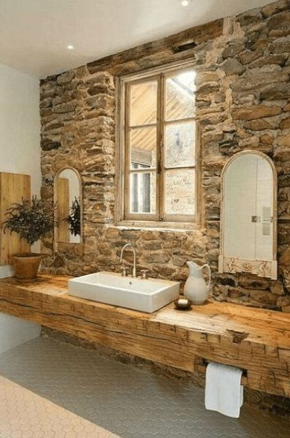 a rough stone wall and a wooden slab floating vanity make up a gorgeous setup for a farmhouse bathroom
