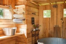 a rustic bathroom of wood, with a galvanized steel bathtub, a vanity with matching steel sinks, some windows