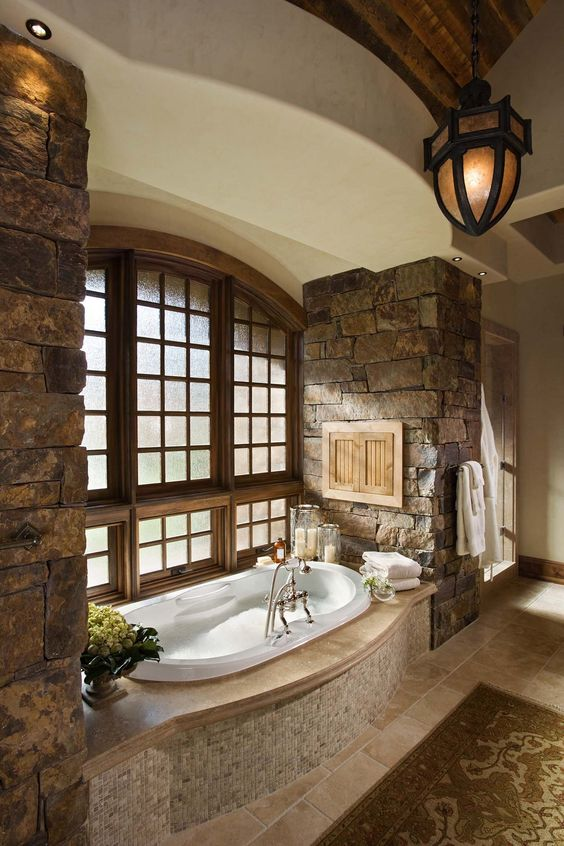 a rustic bathroom with rough stone walls, a built-in bathtub clad with tiles and a vintage lamp