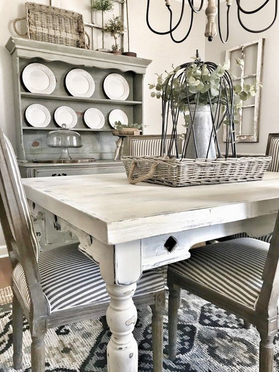 a rustic meets shabby chic dining room with a grey buffet, mismatched neutral furniture, baskets and greenery