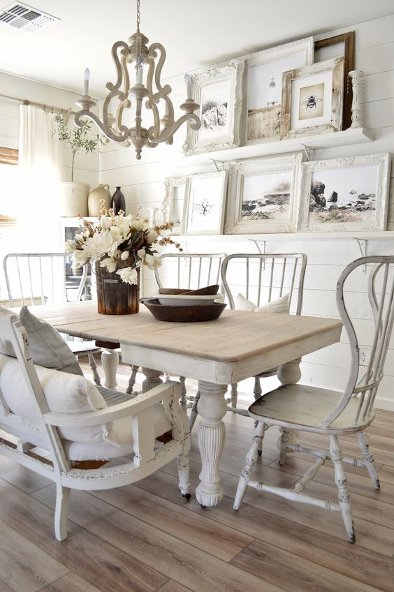 a shabby chic dining room with white shiplap walls, mismatched furniture, a large gallery wall and a vintage chandelier
