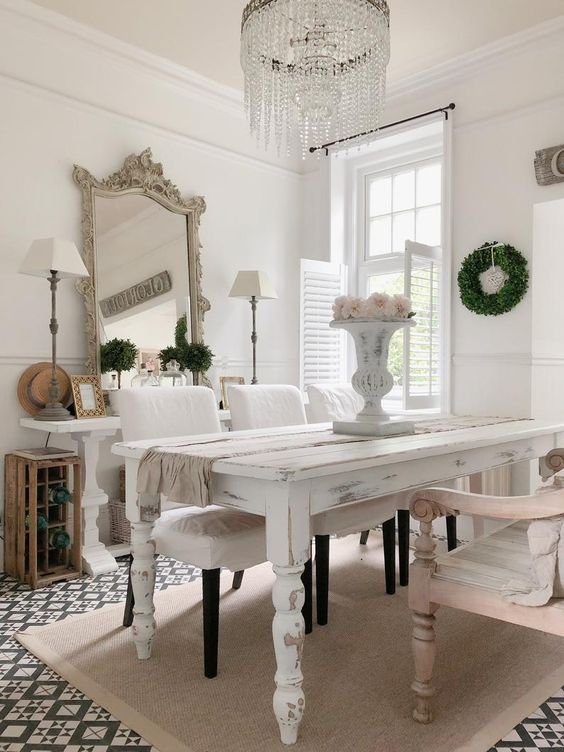 a shabby chic dining space with neutral and pastel furniture, blooms and greenery, a statement crystal chandelier and a refined mirror