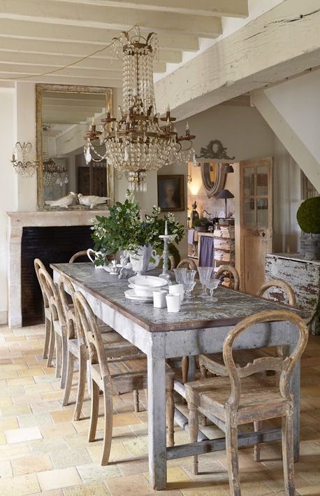 a shabby chic meets French farmhouse dining room with a statement crystal chandelier, shabby wooden furniture and greenery