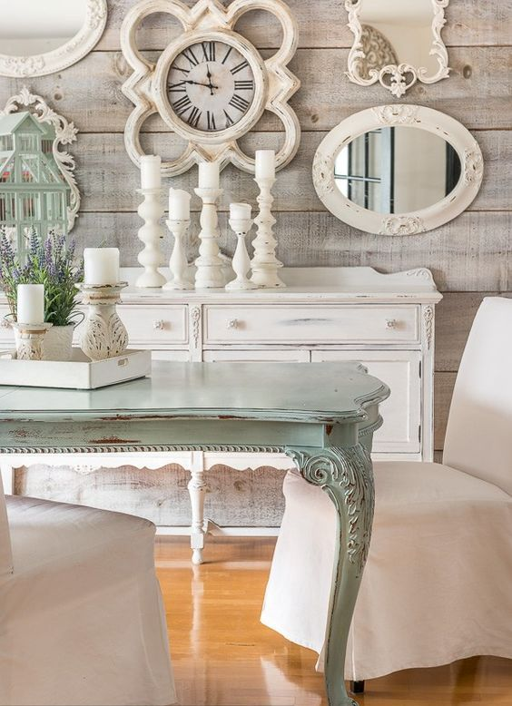 a shabby chic meets rustic dining room with rough wooden walls, a gallery wall with mirrors and art, a mint-colored table and candles