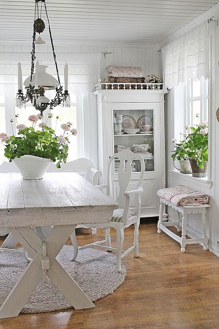 a shabby chic meets rustic white dining room with elegant vintage furniture, an old chandelier and potted plants and blooms