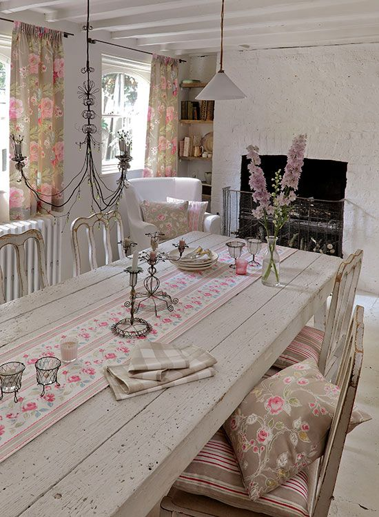 a shabby chic neutral dining room with wooden furniture, a fireplace, pink floral textiles and a vintage chandelier
