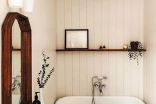 a small and cozy bathroom clad with white planks, a small tub, a vanity with a stone countertop, a mirror in a wooden frame