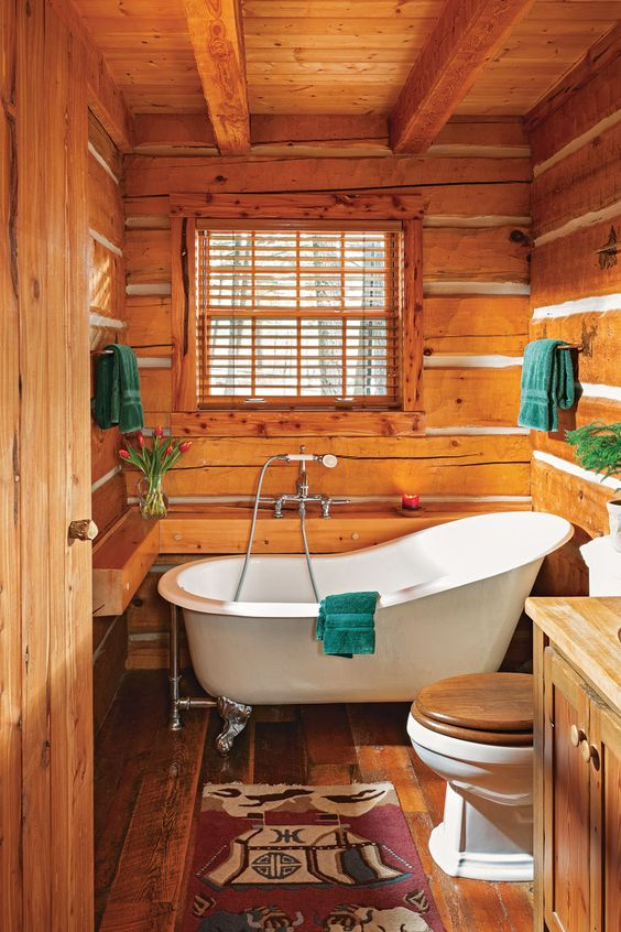 a small cabin bathroom clad with wood, with wooden beams, a wooden vanity, a clawfoot tub and bold textiles