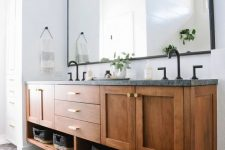 a stylish modern bathroom with a black tiled floor, a floating wooden vanity with a stone countertop, black fixtures and baskets for storage