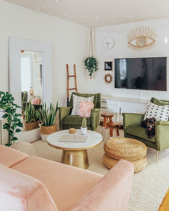 a sweet green and pink living room with potted greenery, jute ottomans, touches of gold and artworks