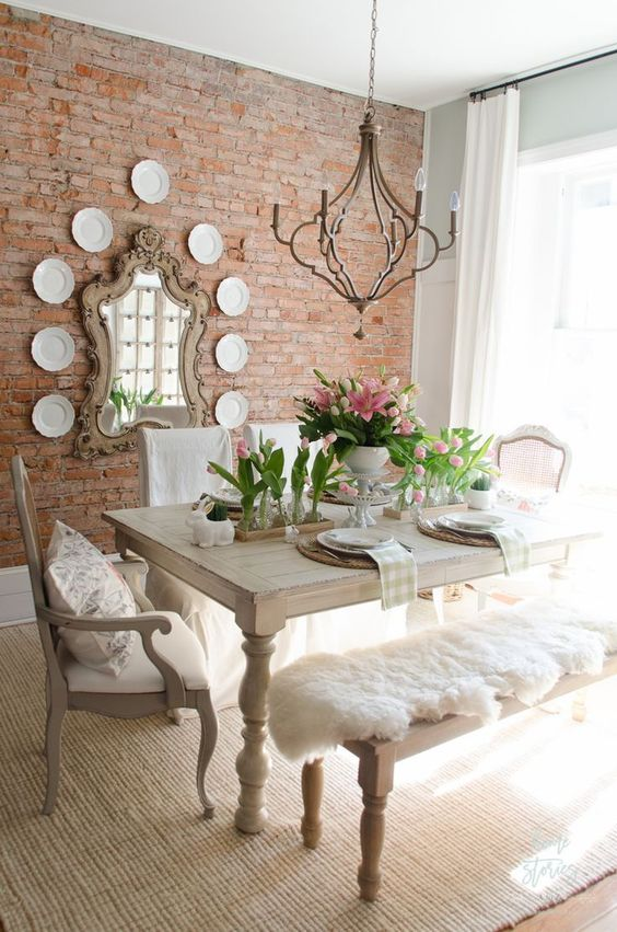 a sweet shabby chic dining room with wooden furniture, pink tulips, a vintage chandelier and a gallery wall with a mirror and plates