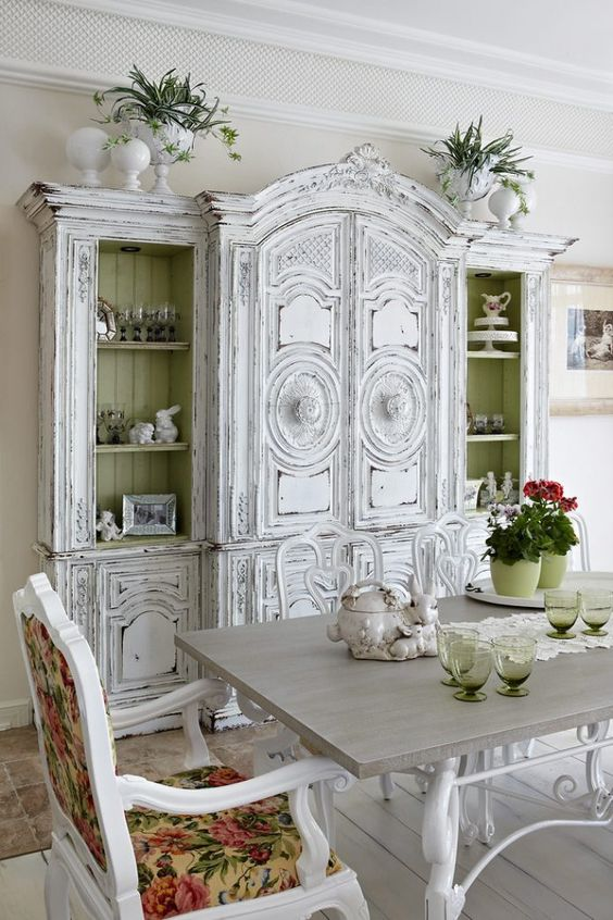 a unique shabby chic dining room with a white buffet, vintage furniture, floral textiles and bold blooms