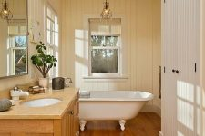 a vintage rustic bathroom with a stained floor and vanity, with painted planked wlals and a ceiling, with sconces and a vintage tub