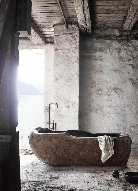 a wabi-sabi bathroom with plaster walls and a bathtub cut out of a stone slab is a unique idea to go for