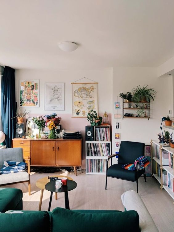 a welcoming living room with navy and green touches, artworks, potted plants, bookcases, lamps and a grey chair