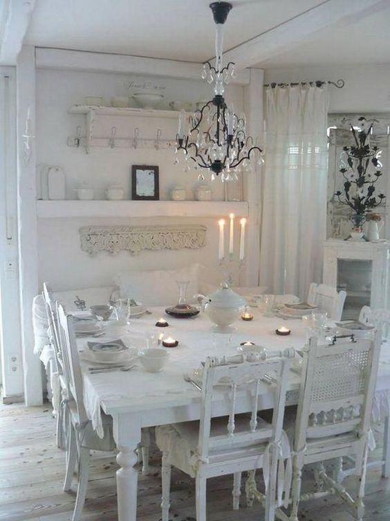 a white shabby chic dining room with lace linens, mismatched chairs, a crystal chandelier and open shelving
