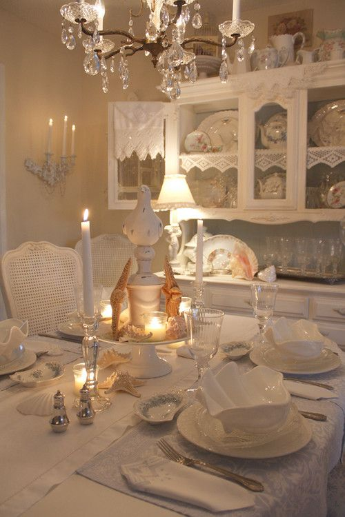 an elegant coastal meets shabby chic dining room with white furniture, a crystal chandelier, candles, starfish, seashells and lace