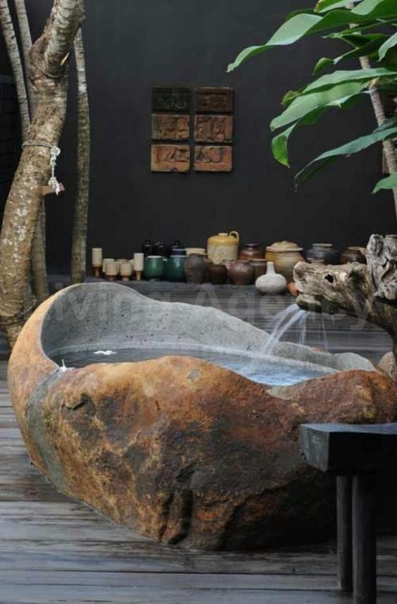 an outdoor tropical bathroom with a bathtub cut out of a stone slab, lots of pots and potted plants