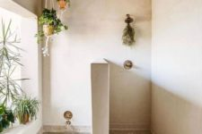 a Moroccan-inspired bathroom with greenery in planters suspended over the tub and on the windowsill