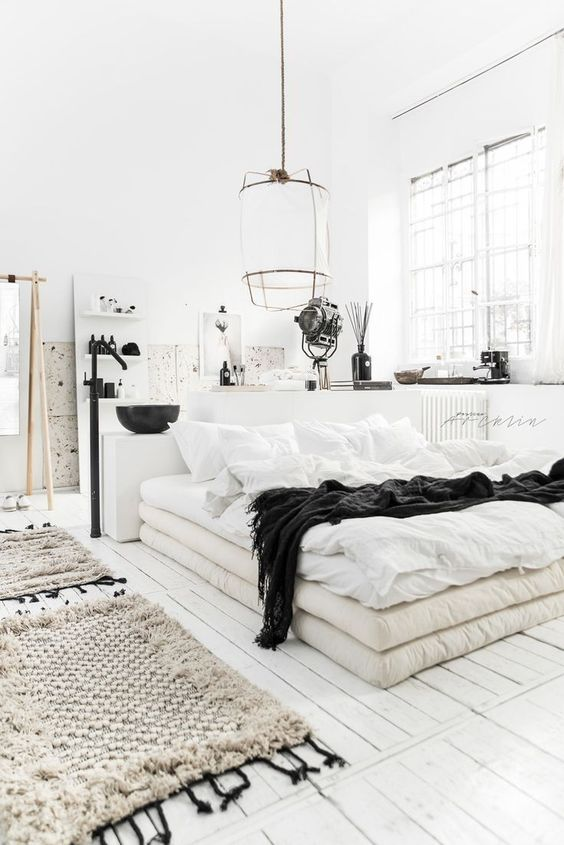 a Scandinavian bedroom with a bed of mattresses, pendant lamps, woven rugs and a bathroom in here