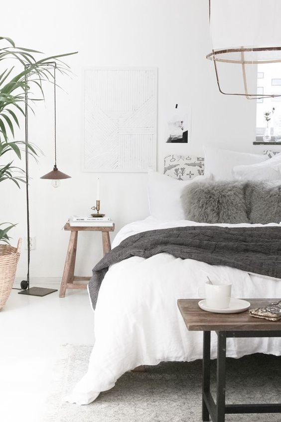 a Scandinavian bedroom with a white bed, some wooden furniture, pendant lamps, artworks and potted greenery