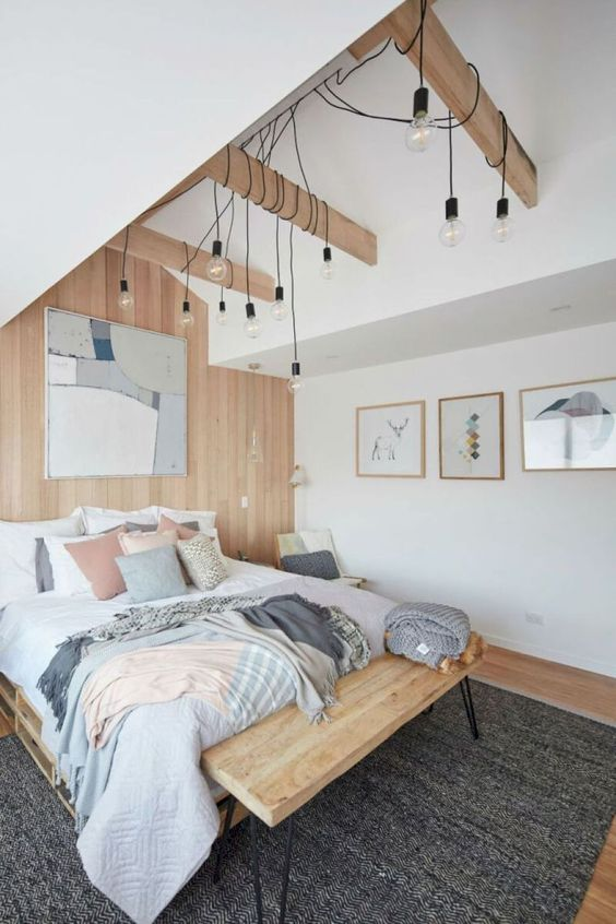 a Scandinavian bedroom with a wooden bed and bench, some bulbs hanging down and pastel touches