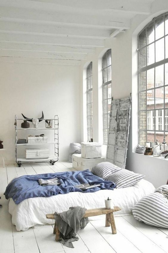 a Scandinavian sleeping space with oversized windows, a shelving unit on casters, a comfy bed and some wooden furniture