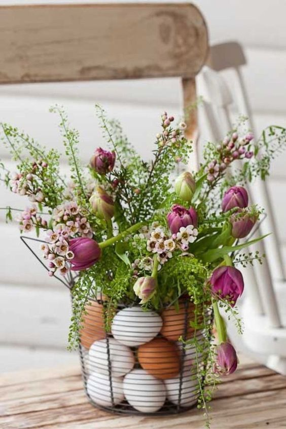 a basket filled with eggs and with greenery and pink blooms on top is a cozy Easter centerpiece