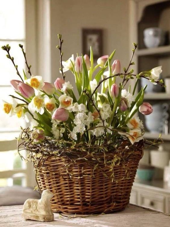 a basket with vines, pink tulips and daffodils, pussy willow is a cool Easter-inspired arrangement