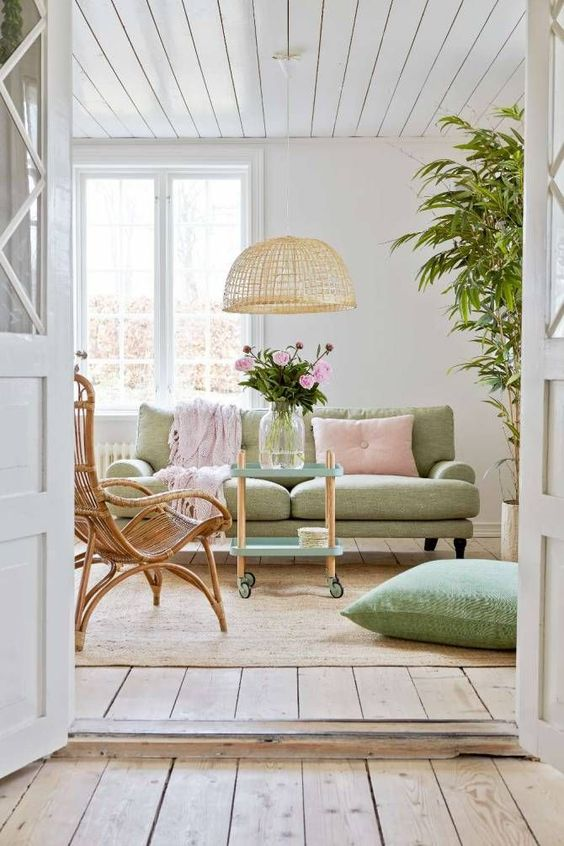 a beautiful pastel living room with a light green sofa and a pillow, a pink pillow and a blanket, a wicker lamp and a rattan chair
