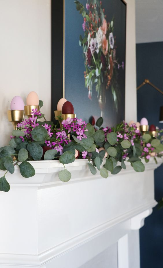 a beautiful spring mantel with lush greenery, blooms and colorful faux eggs in metallic cups for a beautiful look