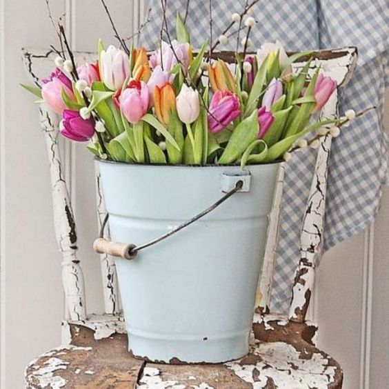 a blue bucket with colorful tulips and pussy willow is ideal for rustic Easter decor